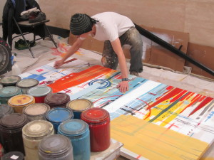 Boettcher Scholar Adam Buehler works on an abstract painting in the lobby of the building at 1515 Arapahoe Street.