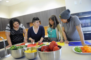 Community members take classes in the community kitchen at the Dahlia campus. (Photo by Chris Schneider Photography)